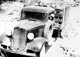 Old b&w image of old truck wih corpsman driving